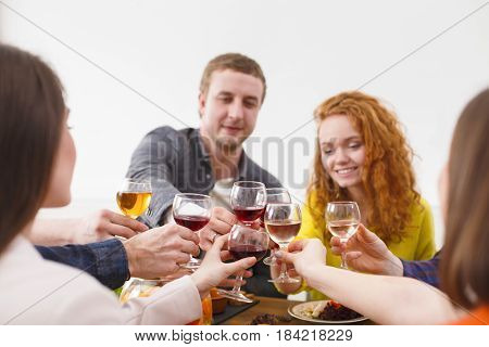 Happy couple celebrate with friends, have dinner in restaurant or at home party. People drink wine together, friendly conversation