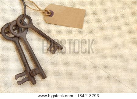Retro background with old keys and paper label on canvas texture