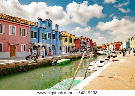 Burano Italy - April 23 2017: Colorful houses by canal in Burano Venice Italy. Burano is an island in the Venetian Lagoon and is known for its lace work and brightly colored homes.