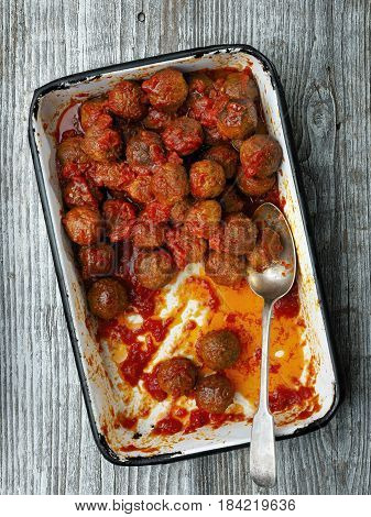 close up of rustic italian meatball in tomato sauce