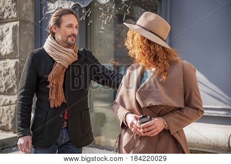 Do not go. Interested middle-aged man is looking at red haired mysterious woman and flirting. They are standing on the street. Man is smiling