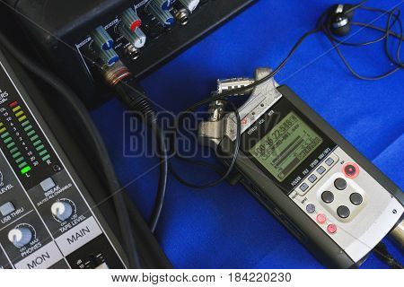 Audio recording equipment, a recorder connected to special equipment for recording the broadcast. Modern technologies in work. Dictaphone and headphones in the recording process.
