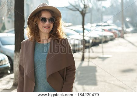 Relaxed lady is walking on street in early spring. She is looking around with enjoyment and laughing. Copy space in right side