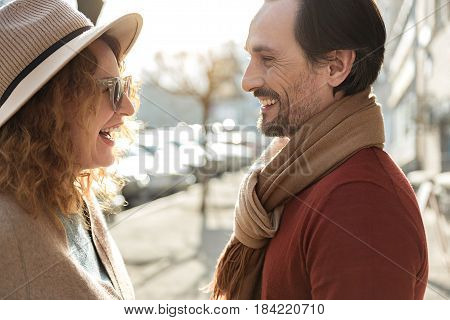 This is the best date ever. Carefree middle-aged couple is looking at each other with love and smiling. They are standing on street with relaxation