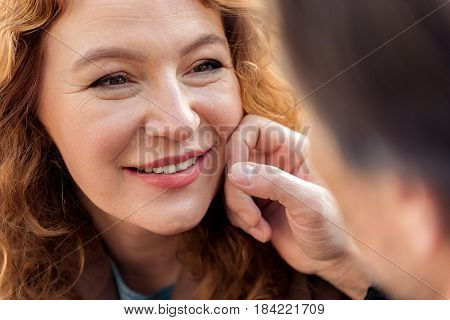 Close up portrait of happy woman enjoying facial touch of her boyfriend. She is smiling with love