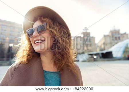 What a wonderful morning. Portrait of cheerful middle-aged woman standing on street and smiling. She is looking around with happiness. Copy space in right side