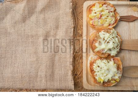 Different topped mini pizza buns on wooden tray