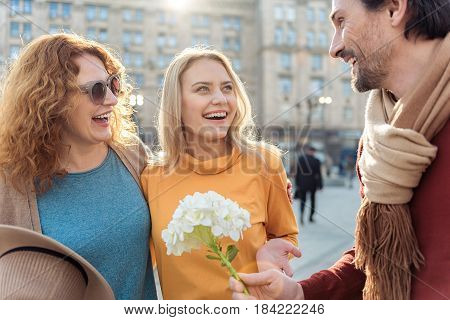 For my loving women. Joyful mature man is giving flower to his wife and daughter. They are standing outdoors and laughing