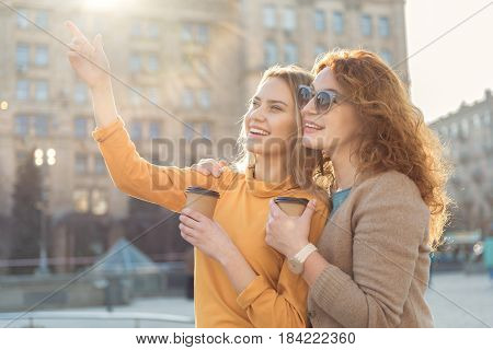 Look at that. Joyful young daughter is pointing finger forward with interest and smiling. Her mother is embracing her while standing on street