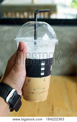 Hand holding Ice cappuccino coffee with milk in cafe