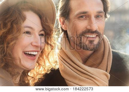 Portrait of happy loving couple relaxing outdoors and laughing. Man is looking at camera with excitement
