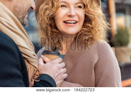 Portrait of excited middle-aged lady relaxing on date outdoors. Man is holding her hand while she is carrying cup of coffee. They are laughing