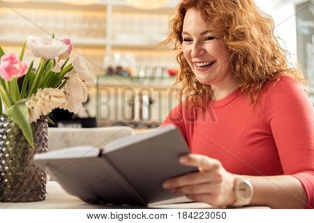 Portrait of joyful middle-aged red haired woman sitting and relaxing in cafe. She is looking into her notebook and smiling