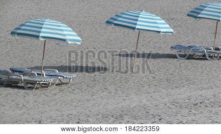 A trio of umbrellas on the beach.