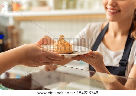 Joyful waitress in giving sweet dessert to customer. She is standing at the counter and laughing. Focus on hands holding cookie