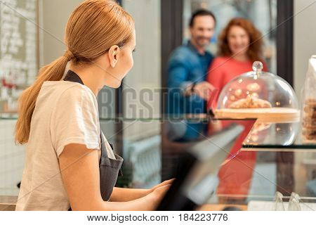 Polite confectionery worker is greeting new customers coming in door. Girl is standing at counter and smiling