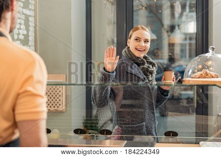 Thank you for service. Glad young woman is waving arm to barista with gratitude while going out the cafeteria. She is holding cup of coffee and smiling