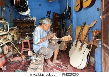 Man Working On Building A Hand Made Guitar At Yogyakarta