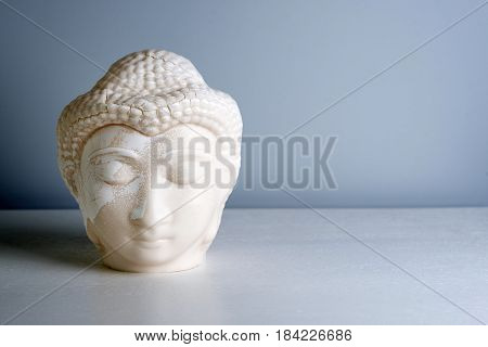 Buddha face. Buddha statue made of white marble with free space for text. Concept of peace, calm and tranquility. Buddhist artifact for Zen style interior decor