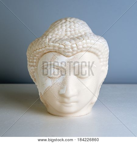 Buddha face. Buddha statue made of white marble. Concept of peace, calm and tranquility. Buddhist artifact for Zen style interior decor