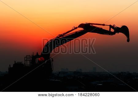 Excavator loader model with silhouette on sunset at over city buildingConcepts Double exposure