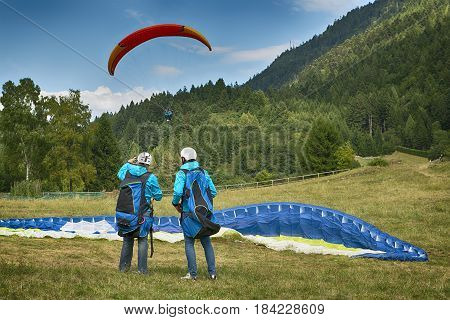 Two paragliders just landed on the lawn in summer season near little village of Molveno