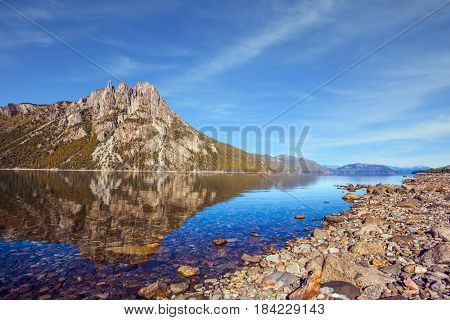 Mountain in Bariloche, Argentina. The water of shallow lake reflects sharp rocks. The concept of exotic and extreme tourism