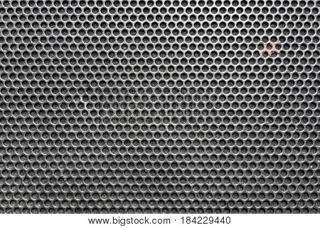Metal honeycomb grilled pattern in front of music speaker as background.