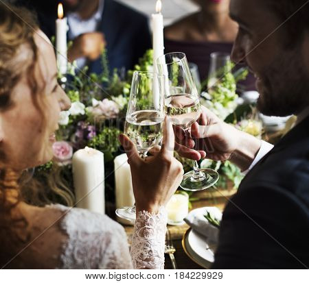 Bride and Groom Clinging Wineglasses Together at Wedding Reception