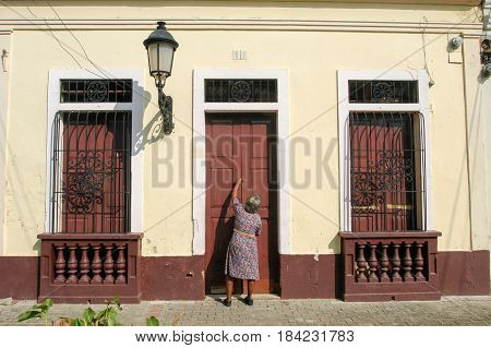 Santo Domingo, Dominican Republic - 3 february 2002: woman opening the entrence door of her colonial house at Santo Domingo on Dominican Republic