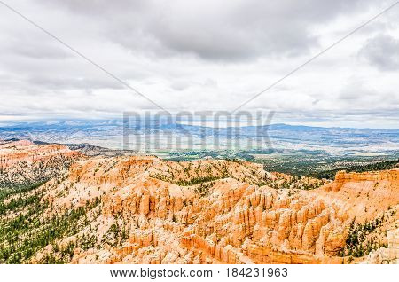Hoodoos with pine trees and storm clouds at Bryce Canyon National Park in Utah.