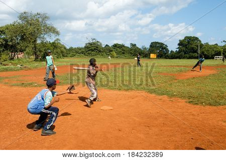 Boys Playing Baseball On A Field At Las Galeras