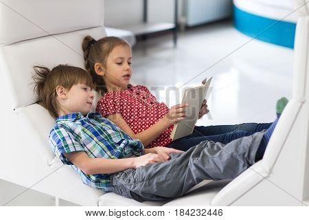 Pretty little girl and boy are reading book.