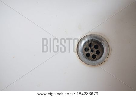 Closeup of stainless steel drain of white washbasin background
