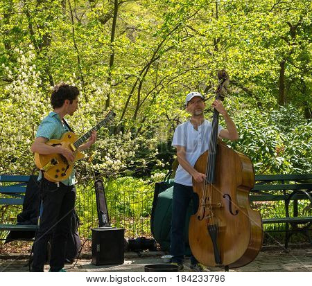 New York NY USA -- April 28 2017 -- An electric guitar and upright Bass player performing musically in New York's Central Park. Editorial Use Only.