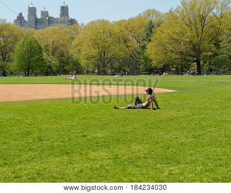 New York NY USA -- April 28 2017 -- Man relaxes on a baseball field on a Spring day in Central Park. Editorial Use Only.