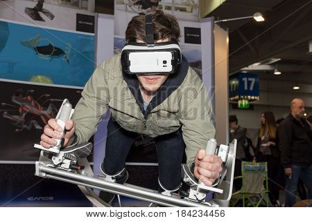 Hannover Germany - March 22 2017: A young man plays with a virtual reality flying skydiving frame of the company Icaros at Cebit 2017. CeBIT is the world's largest trade fair for information technology.