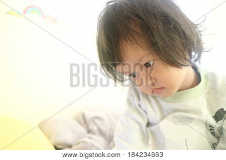 Little baby boy waked up and sitting on the white bed