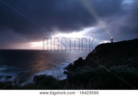 lighthouse at the time of dramatic stormy sunset
