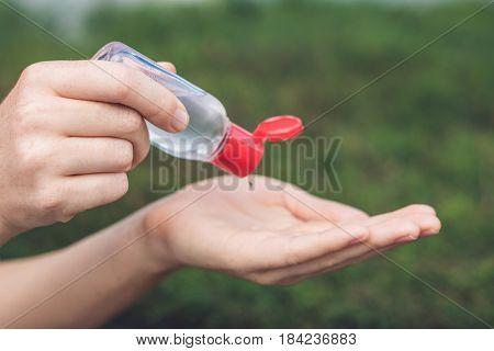 Women's Hands Using Wash Hand Sanitizer Gel Pump Dispenser