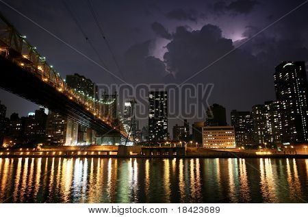 New York. Night view of the Queensborough Bridge before the storm, with lightning in the sky.
