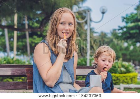 Mom And Son Eat Fried Sweet Potatoes In The Park. Junk Food Concept