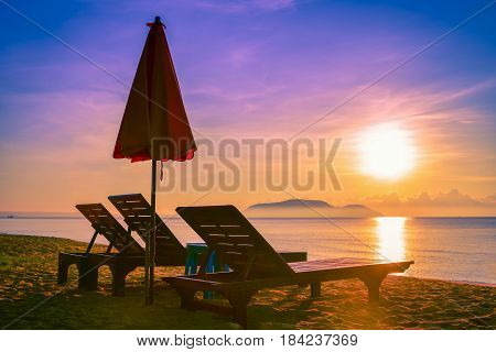 Landscapes of sunset on colorful sky background and silhouette beach umbrella and chairs on the beach.