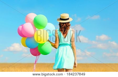 Back View Happy Woman Stands With An Air Colorful Balloons In A Straw Hat Enjoying A Summer Day On A