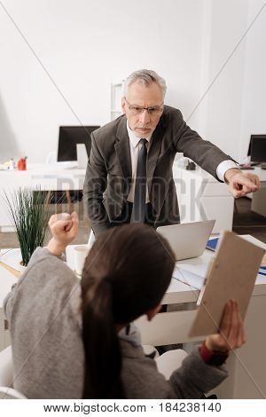 I said so. Confident office worker standing near his workplace raising his left arm while looking at his manager