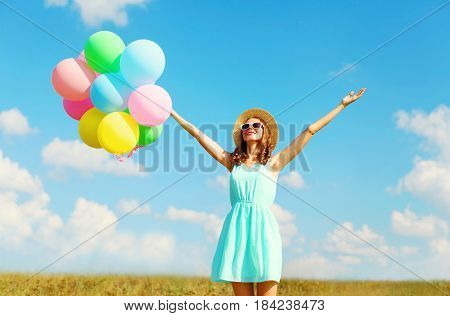Happy Young Smiling Woman With An Air Colorful Balloons Is Enjoying A Summer Day Over Blue Sky Meado