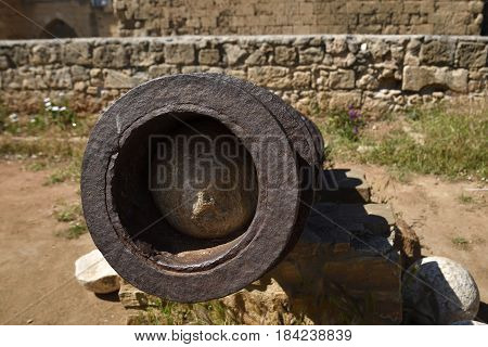 Close-up from front of a old cannon with a cannon-ball inside and a old brickwall in background picture from the North of Cyprus.