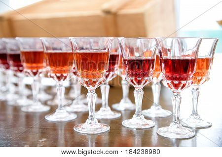 Crystal wine glasses with different liquids on wooden table.