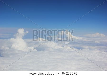 the view from the window of the plane, figures out of clouds high in the sky, a soft carpet of clouds with elevations, one figure similar to a snowman, you can see the hand, turned to the side