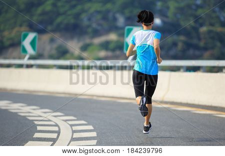 Healthy lifestyle young fitness woman running at city road